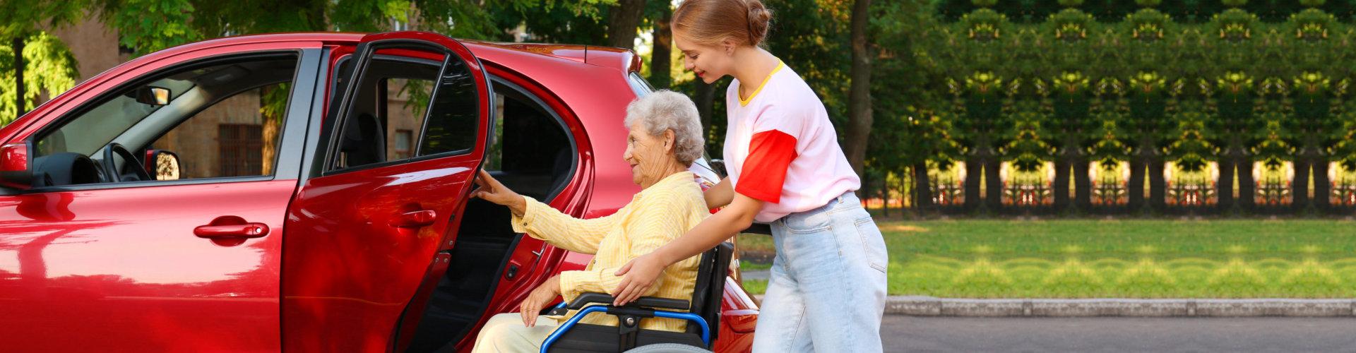 woman helping a senior woman get inside the car